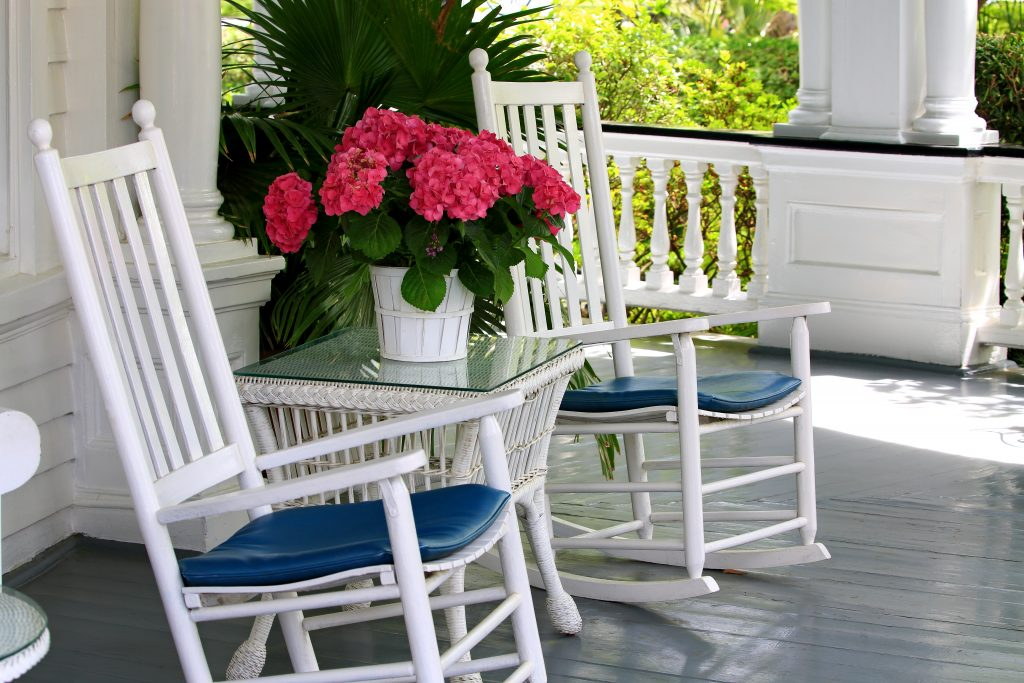 two white rocking chairs on a porch with a bouquet of pink flowers between them