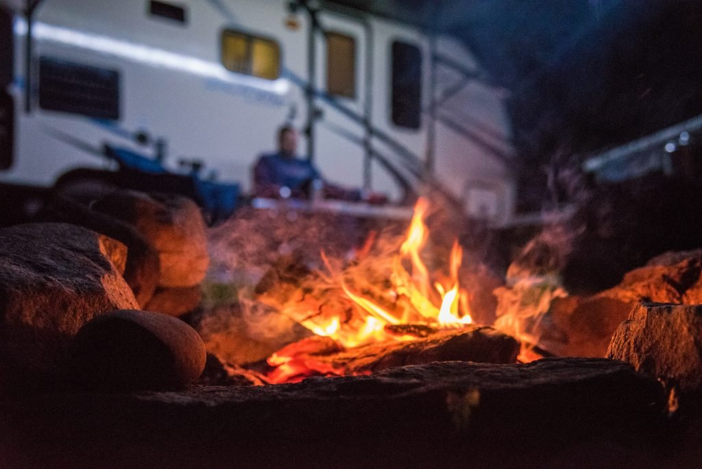 RV at a campsite at night with a campfire in the foreground