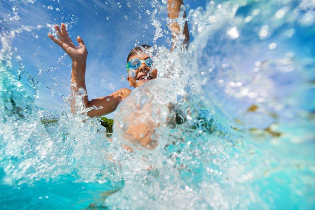 young boy splashing water in a water park