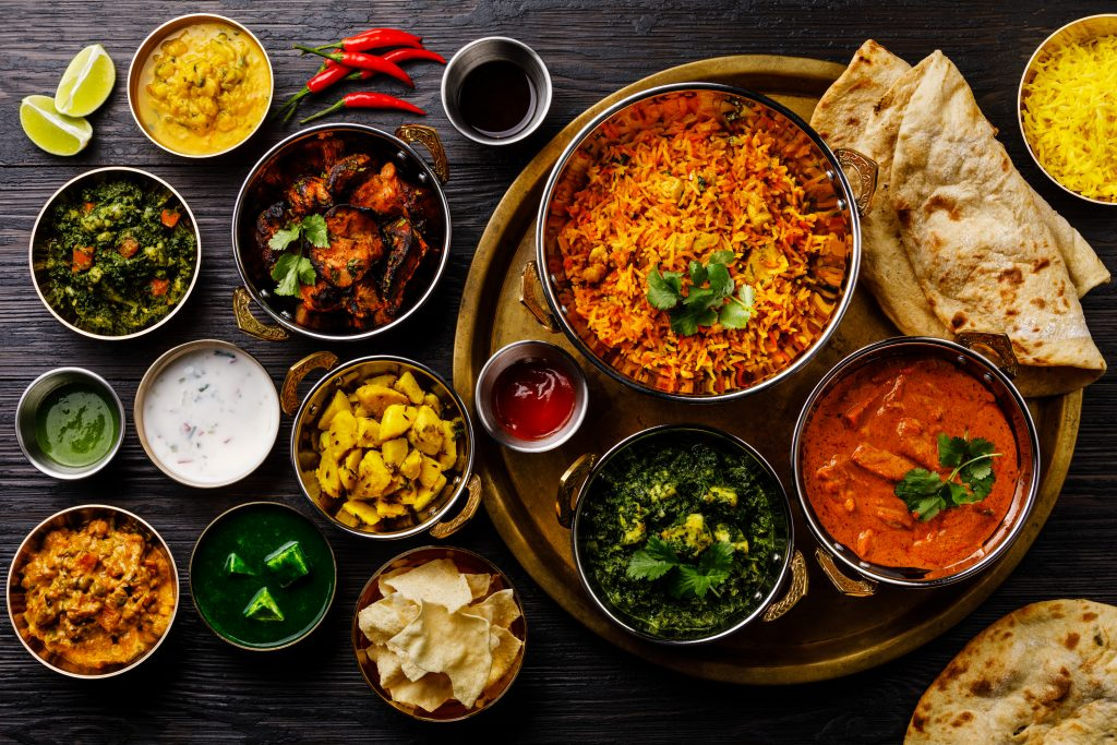 spread of dallas indian food with many chutneys shot from above