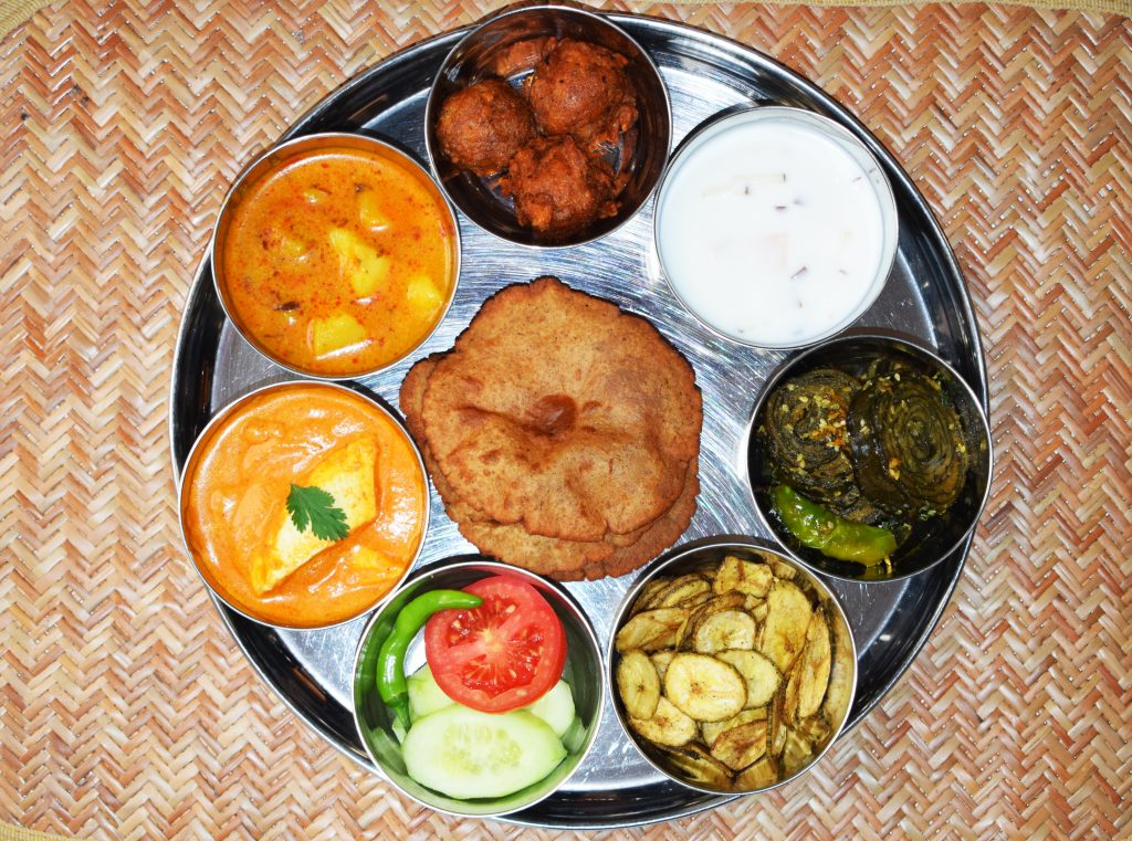 thaali platter shot from above with multiple chutneys