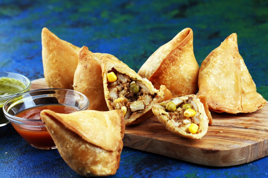 Indian samosas served on a wooden platter, one of the best indian foods in dallas