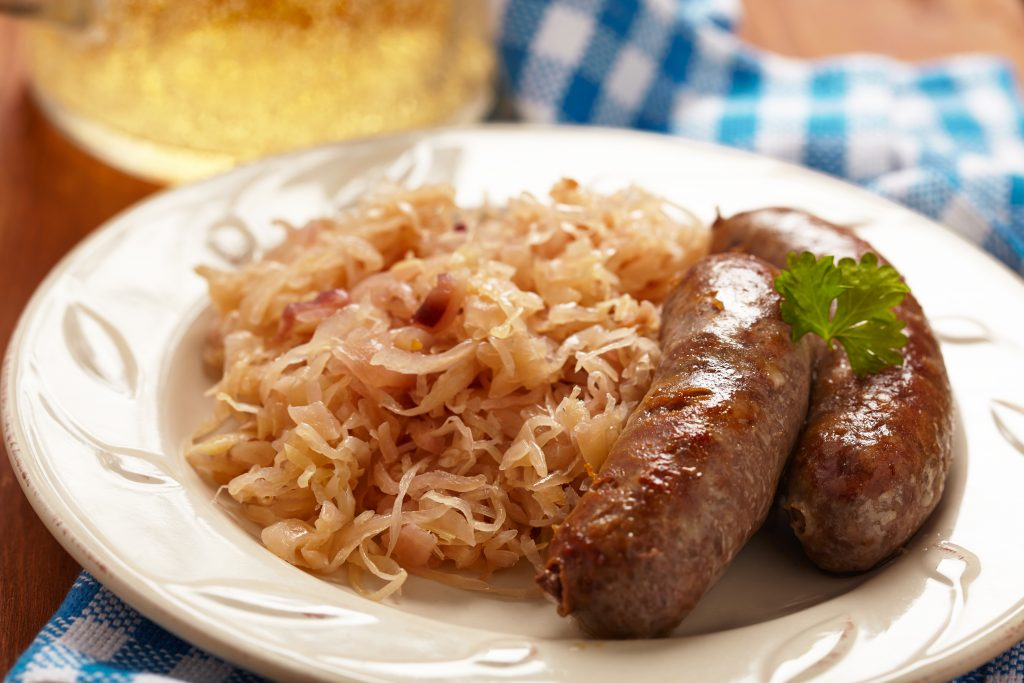 white plate with 2 german sausages and sauerkraut. wurstfest belongs on any list of what to do in new braunfels tx