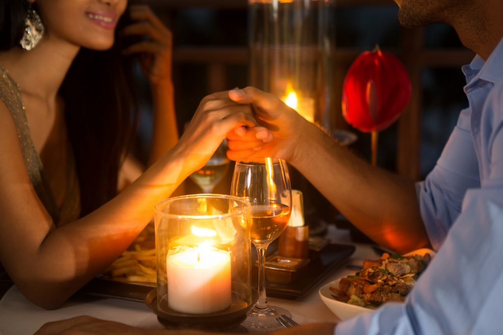 couple holding hands over the dinner table lit with candles. romantic private dinners are available at some jefferson tx bnbs