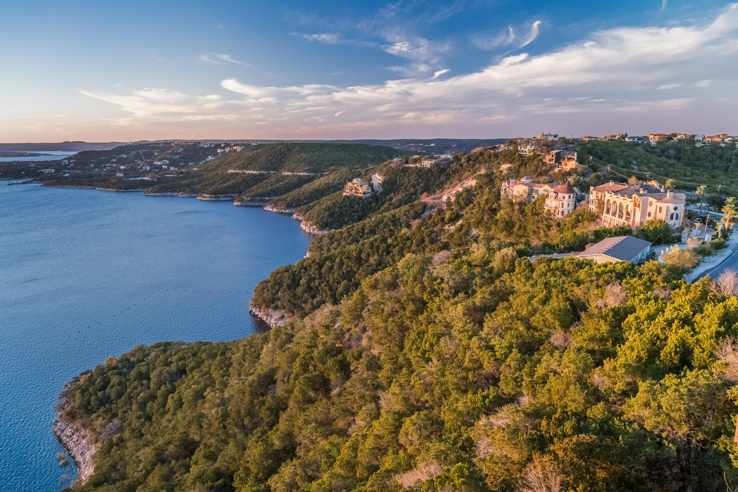 View of Lake Travis Austin Texas from above with green cliffs on the right and blue water on the left