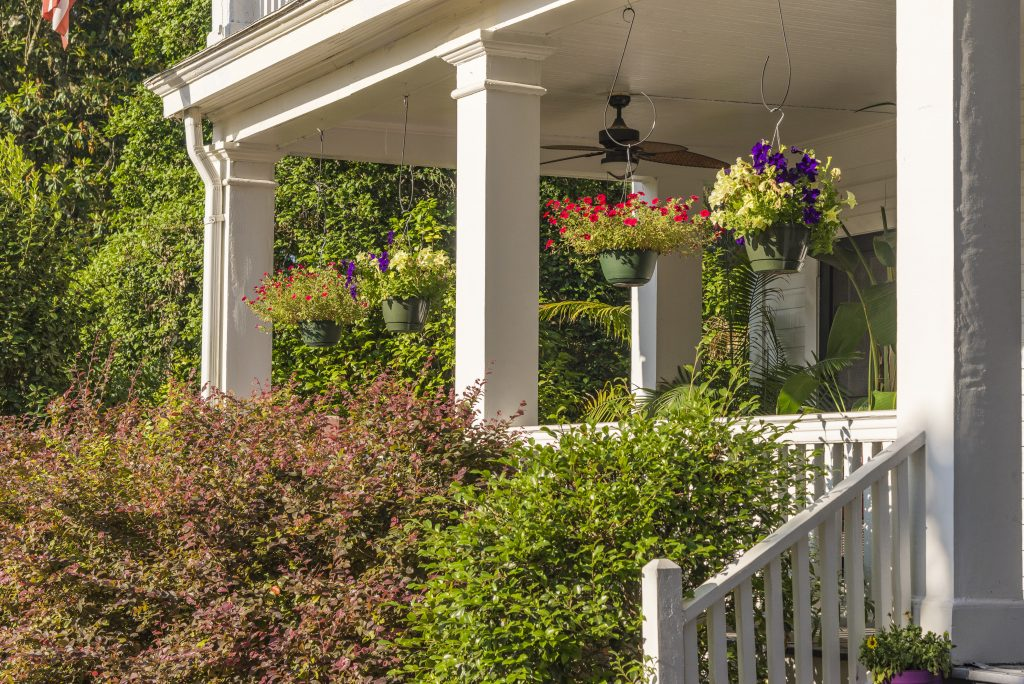 white front porch with flower baskets hanging from it. many of the best bed and breakfasts in jefferson texas have front porches to enjoy