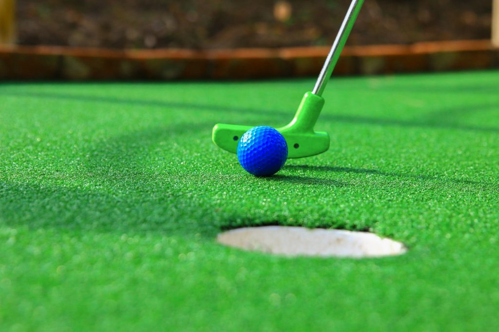 green mini golf putter pushing a blue ball. mini golf is one of the best things to do in corpus christi with kids