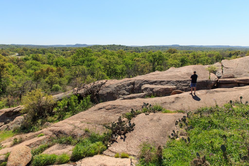 man hiking on enchanted rock texas hill country in the background
