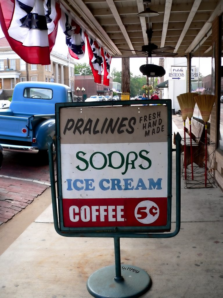 sign advertising pralines sodas ice cream coffee in front of the jefferson general store, one of the best jefferson attractions