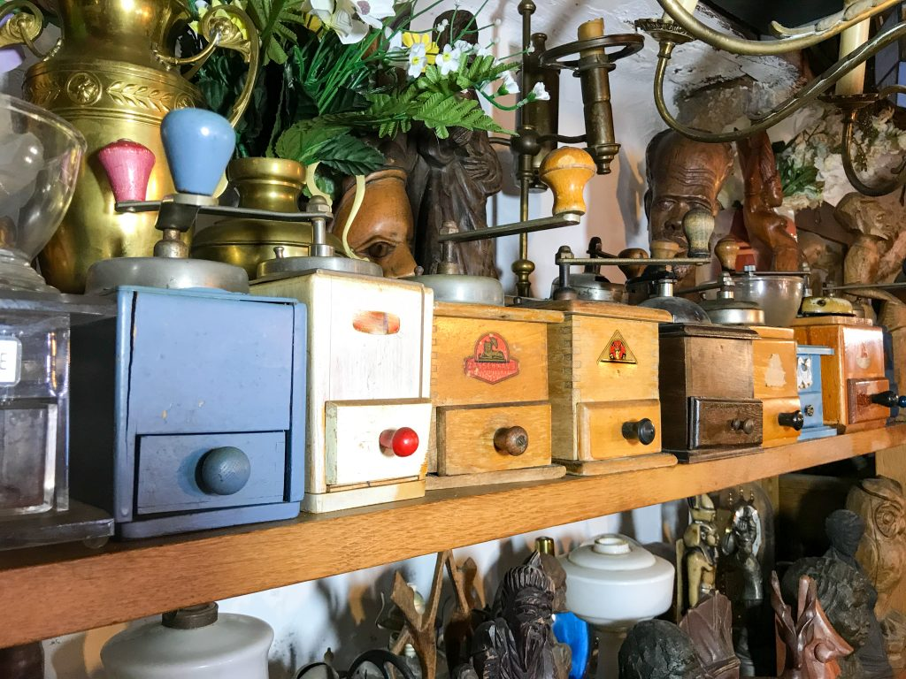 interior of an antique shop with small wood chests on a shelf. antiquing is one of the best things to do in jefferson texas