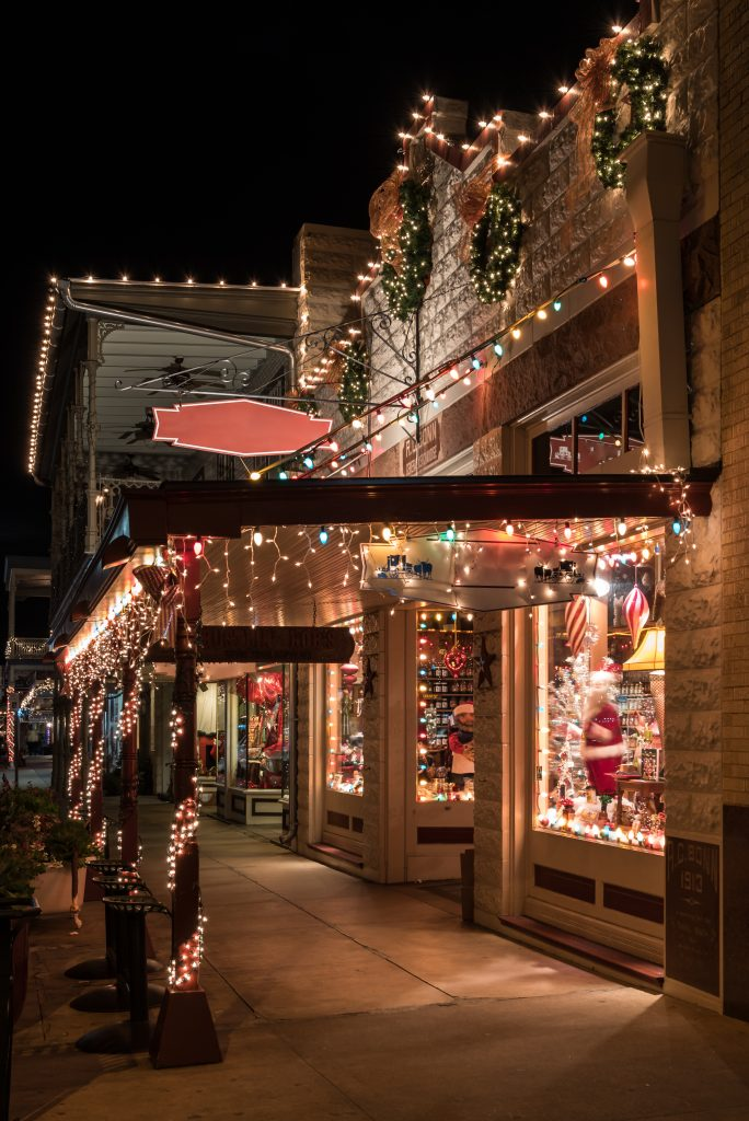 storefront in a small texas christmas town at night lit up with lights