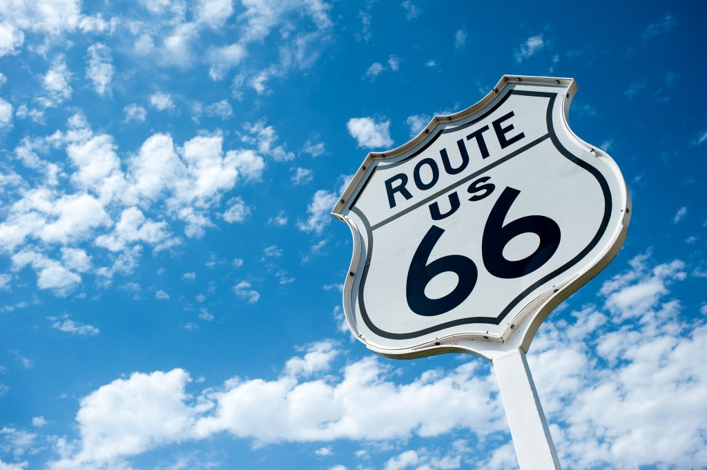 "White sign with black text reading ""us route 66"""