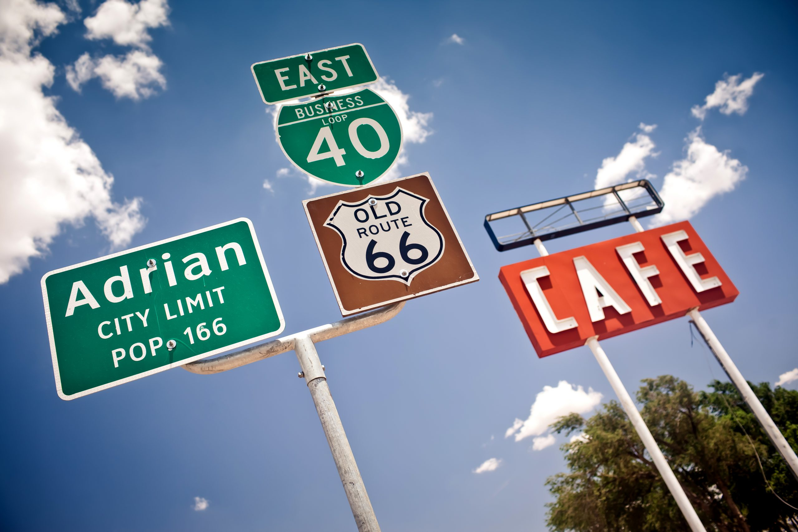 Road signs along Texas Route 66 with Midpoint Cafe sign in the background