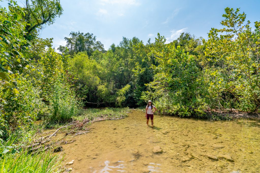 Kate Storm standing in the creek at St Edwards Park, one of the best hiking trails in Austin