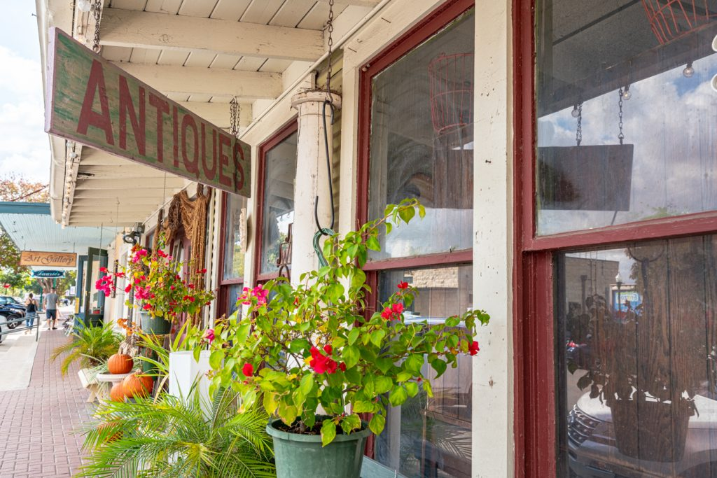 "front facade of an antique shop with flowers blooming out front and a hanging sign that reads ""antiques"""