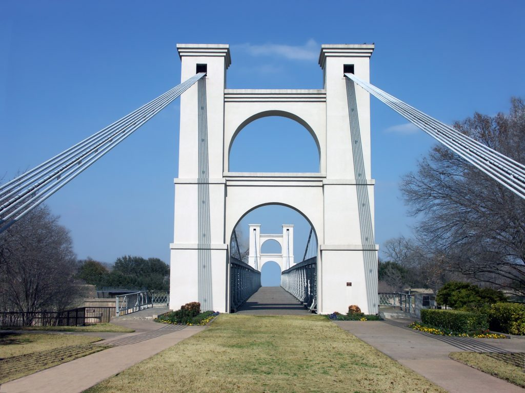 view of waco suspension bridge from a park. waco is one of the best places to spend spring break in texas