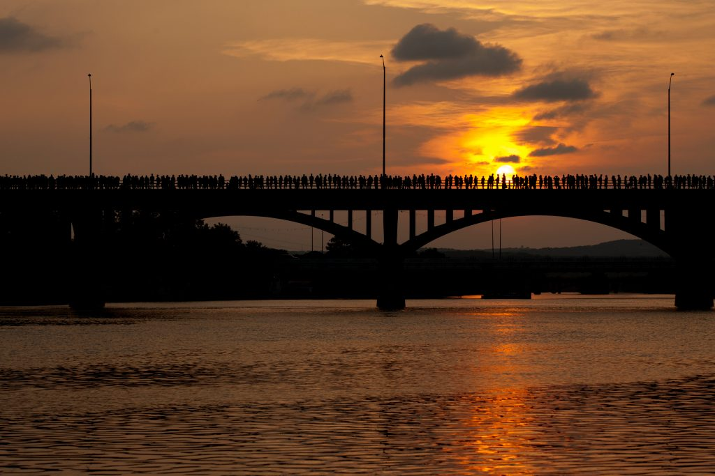 south congress bridge in austin texas at sunset as seen from across the water with spectators waiting for bat colony on it