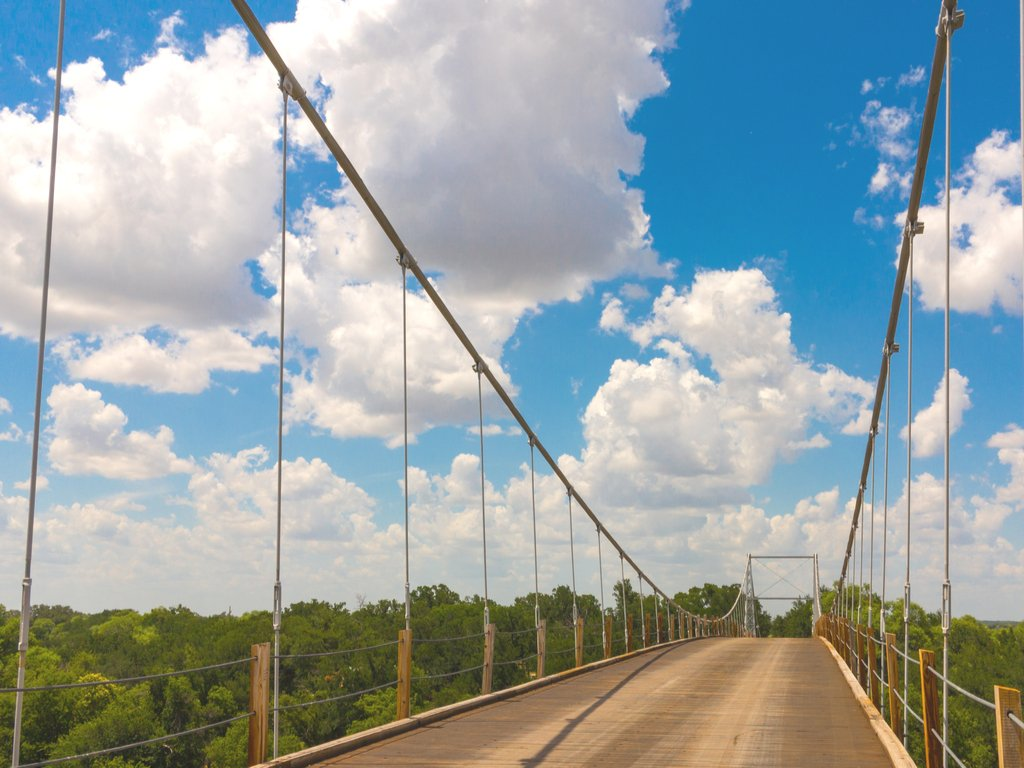 regency bridge in san saba county as seen from the bridge on a partly cloudy day