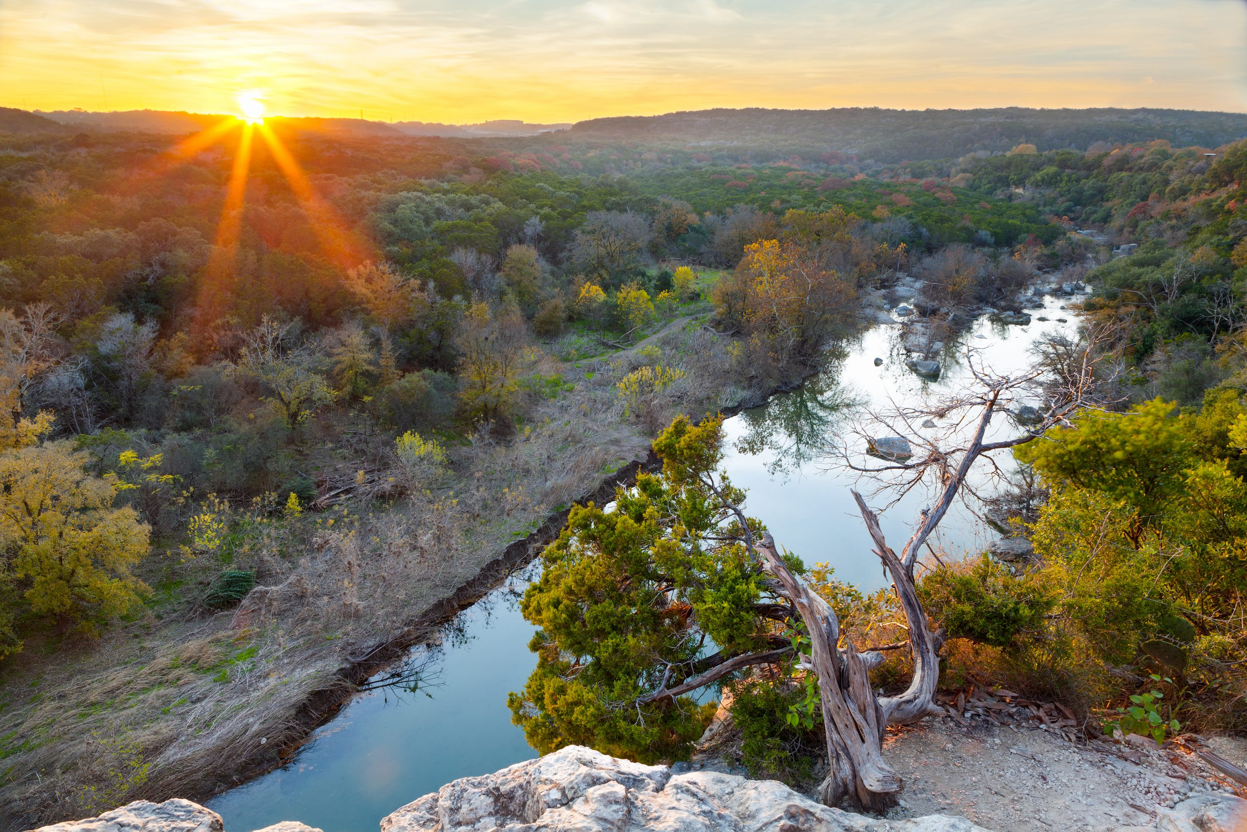 sun setting over barton creek greenbelt, one of the best places to go hiking in austin texas