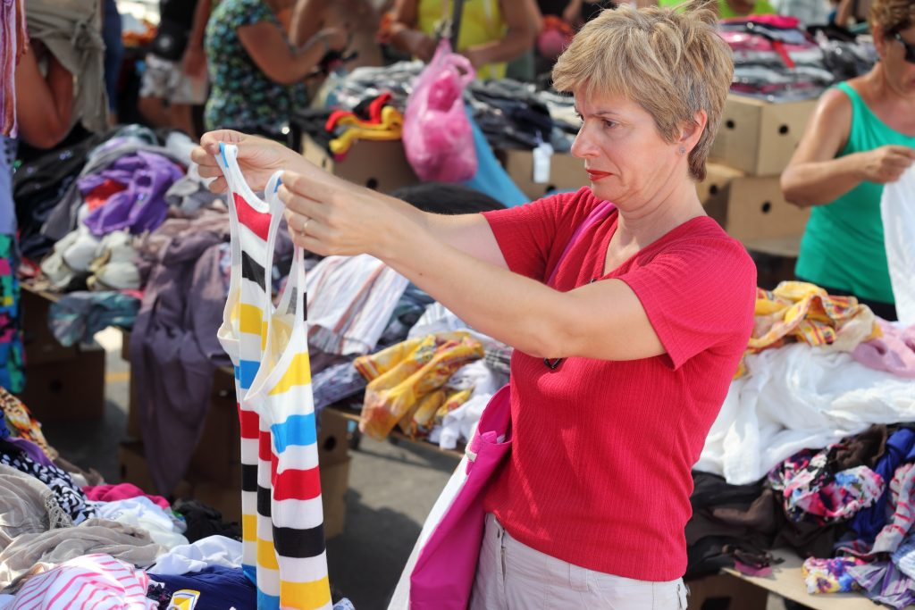 woman with short blond hair holding up a tank top from a pile at one of the texas flea markets