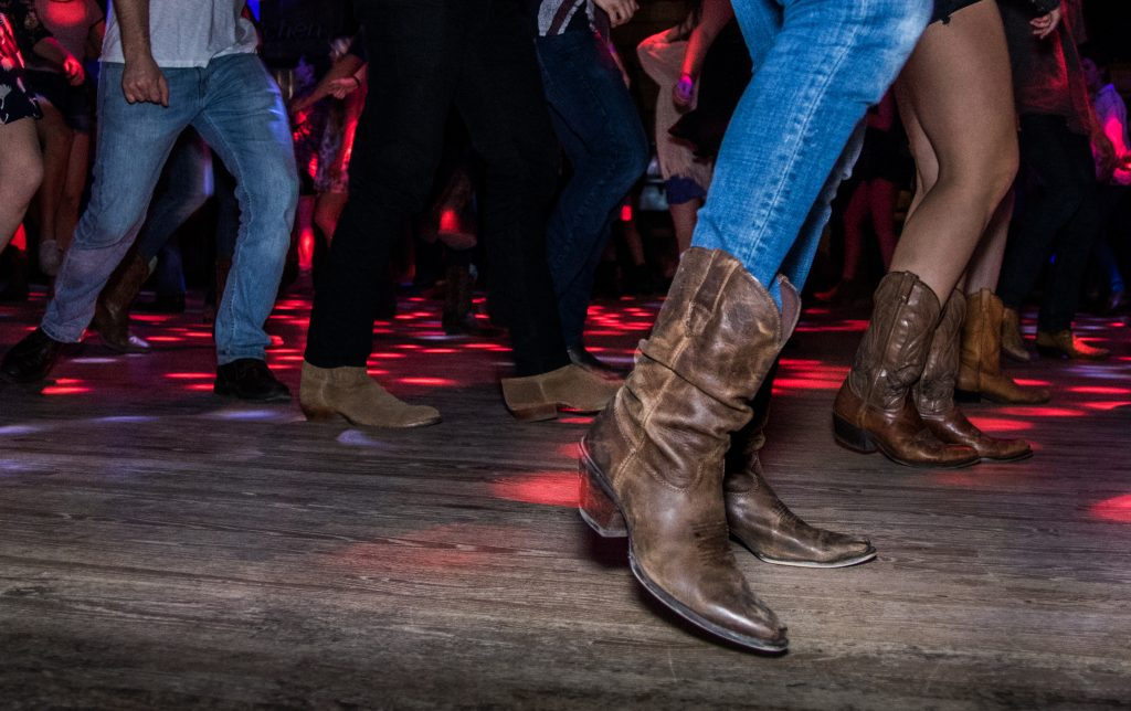 people wearing cowboy boots and western clothes dancing on a wooden floor in a texas dance hall