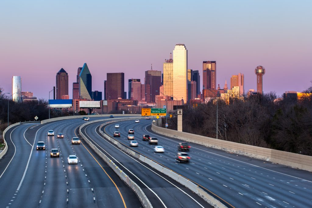 freeway in dallas texas with the skyline in the background. large interstate views like this are common when driving from dallas to san antonio texas