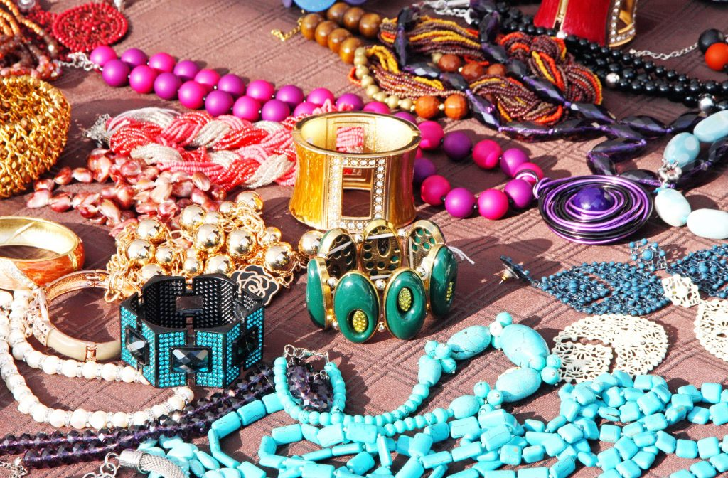 collection of colorful vintage jewelry laid out for sale on a table