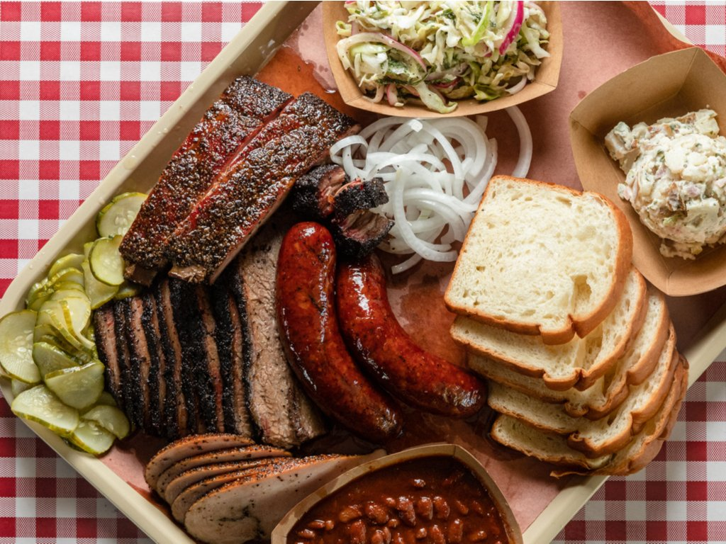 plate of texas barbecue as shot from above on a checkered table cloth. food is one of the best reasons to visit texas