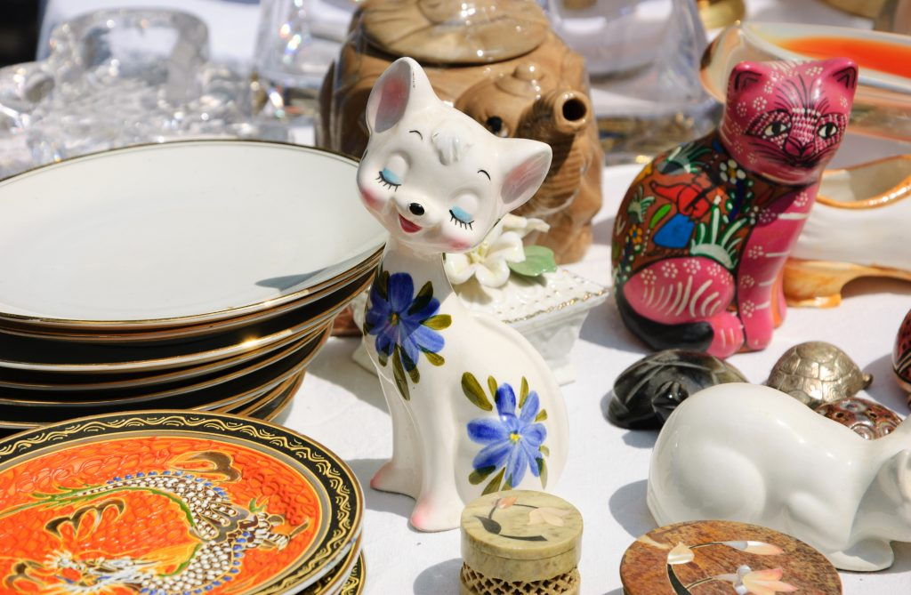 small antique cat figurine surrounded by antique dishware