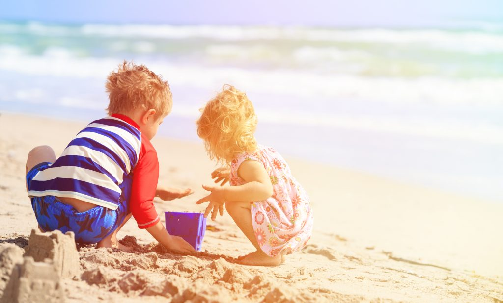 two small children playing in the sand on one of the best beaches in corpus christi tx