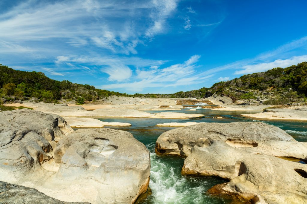 river moving over limestone on a sunny day in pedernales falls state park, one of the texas state parks near austin