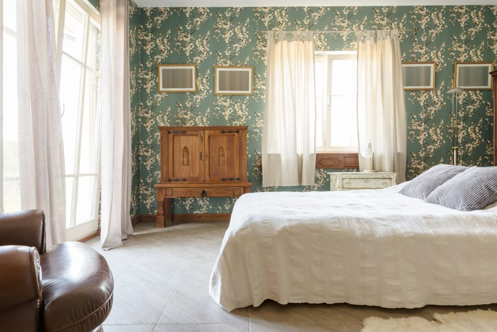 bedroom in a historic inn with teal wallpaper and white linens. historic bed and breakfasts in fredericksburg tx are among the best places to stay