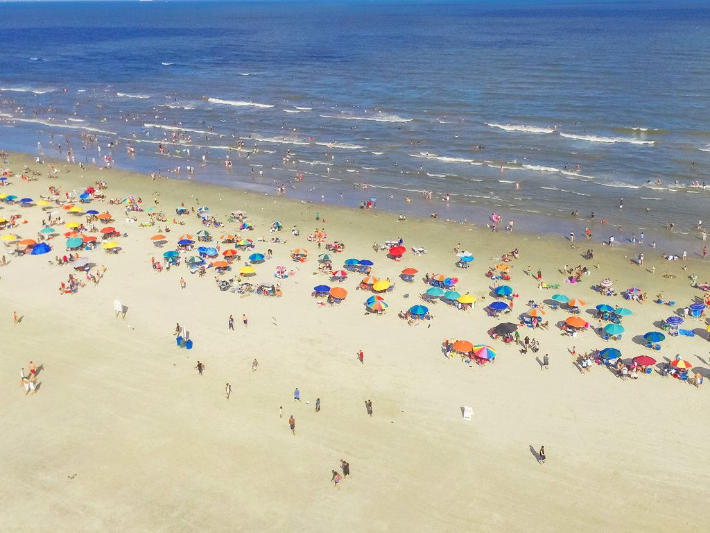 aerial view of colorful umbrellas and crowds in galveston, home to some of the best beaches in texas