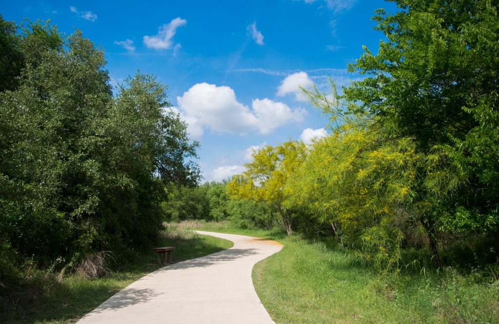 paved hiking trail in san antonio texas lined by trees