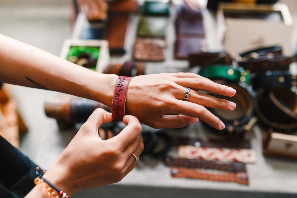woman's hand outstretched as she tries on a leather bracelet at a craft fair