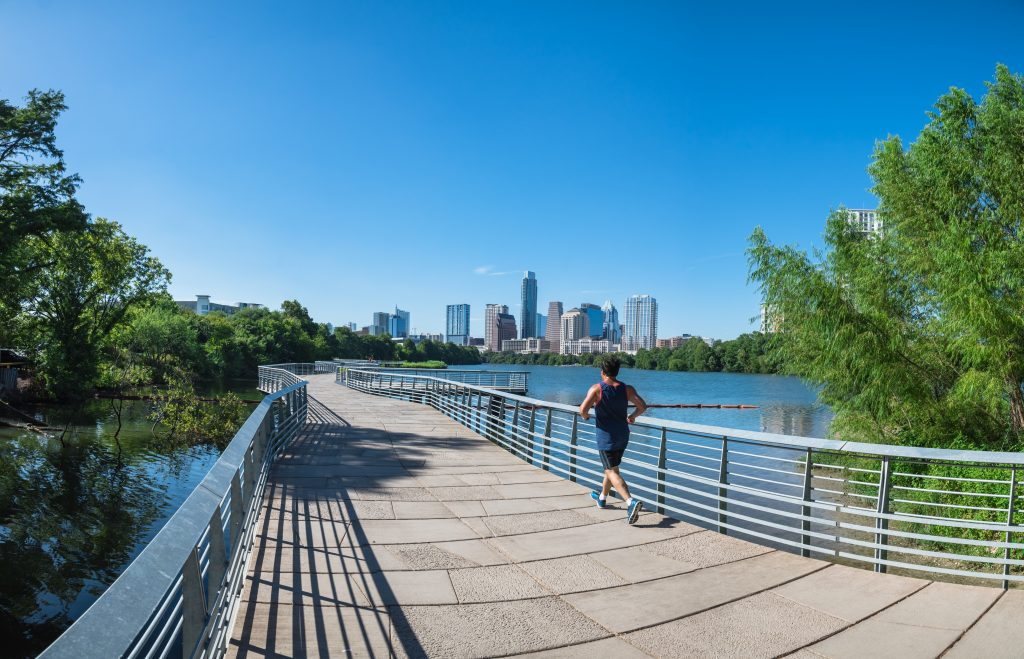 Woman jogging on the boardwalk on the hike and bike trail with the skyline in the distance