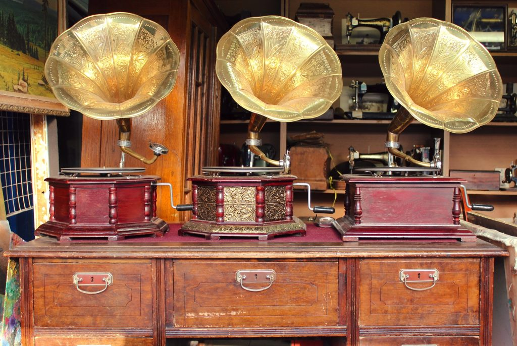 3 antique gramophones sitting on a wooden desk--you'll want to be prepared to haul purchases like this home from the best texas flea markets
