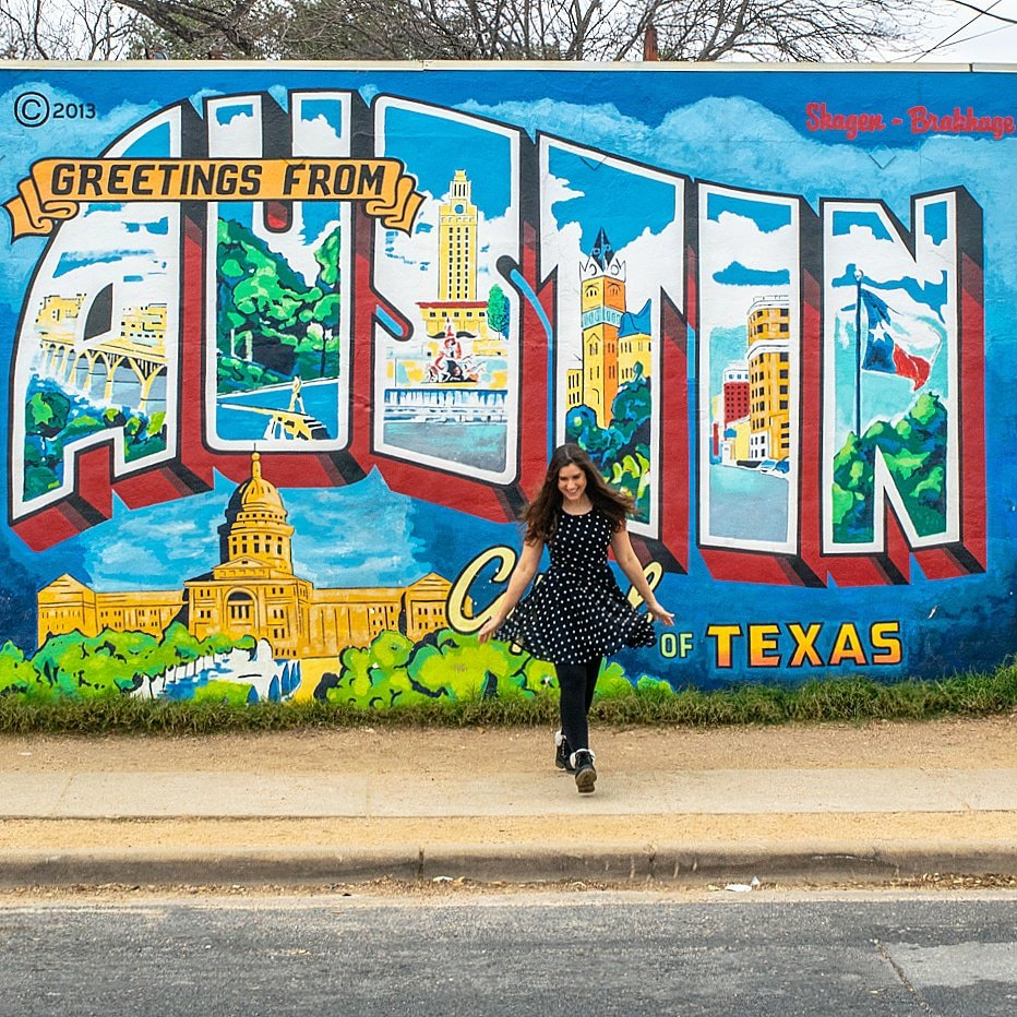 kate storm standing in front of the greetings from austin mural on a cloudy day in january