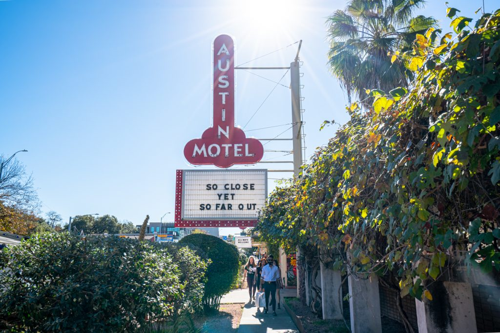 """austin motel sign reading """"so close yet so far out"""", one of the most iconic places to stay in austin tx"""