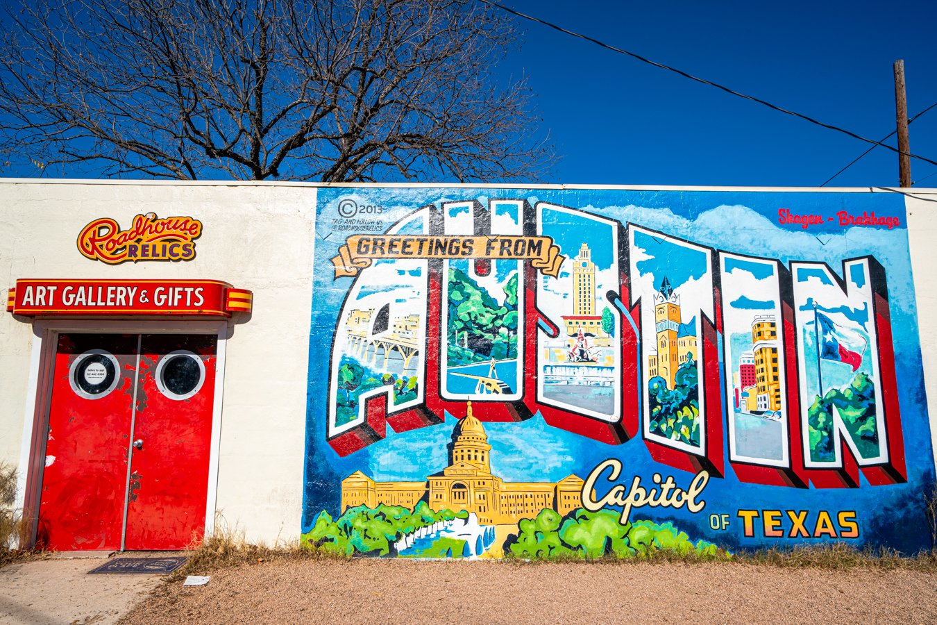 greetings from austin mural on a sunny day with red roadside relics doors to the left