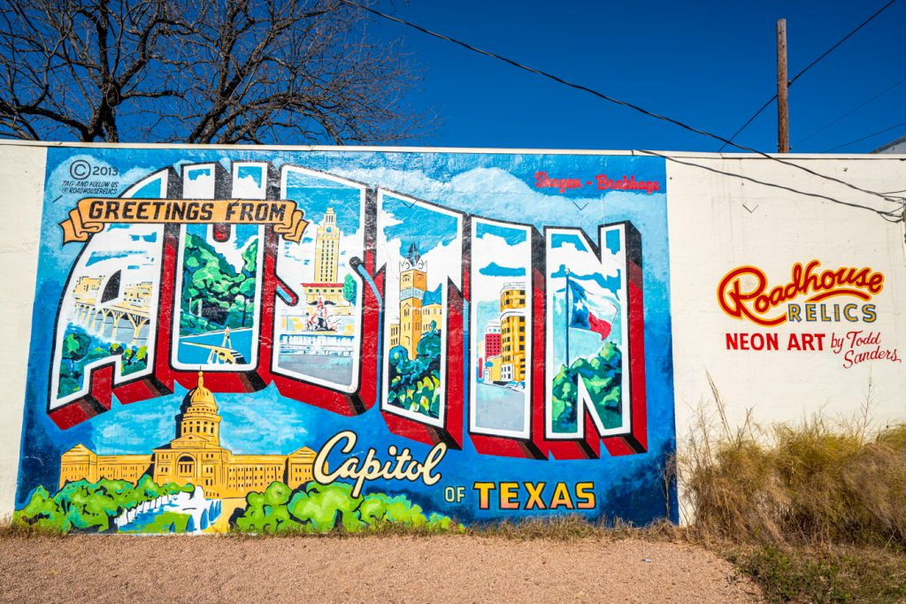 greetings from austin mural with roadside relics sign to the right