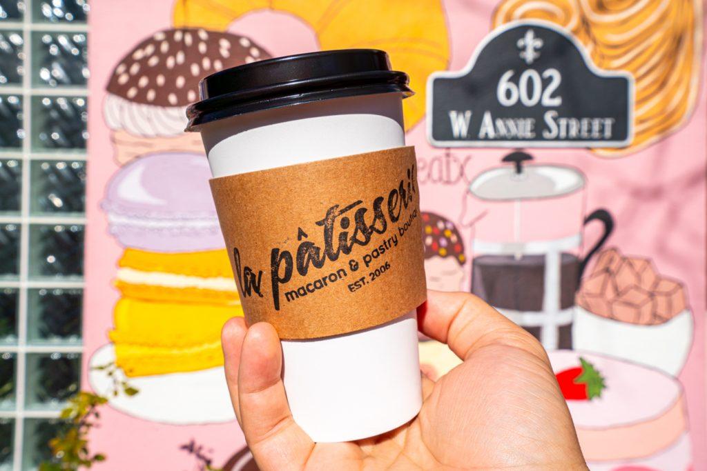 la patisserie coffee cup being held up in front of paintings of pastries on a pink background