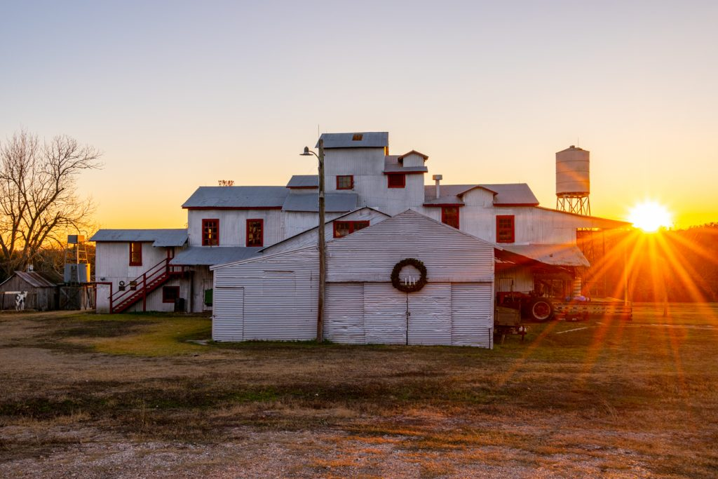 1914 burton farmers cotton gin at sunset with a sun flare to the right