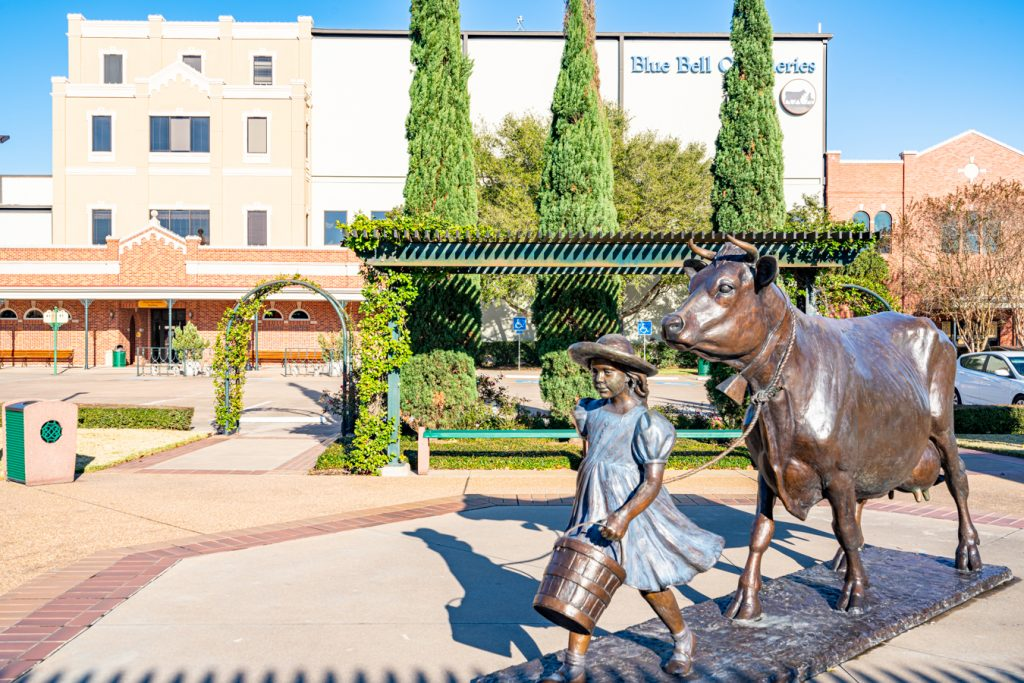 exterior of blue bell breham texas with a statue of a girl leading a cow in the foreground