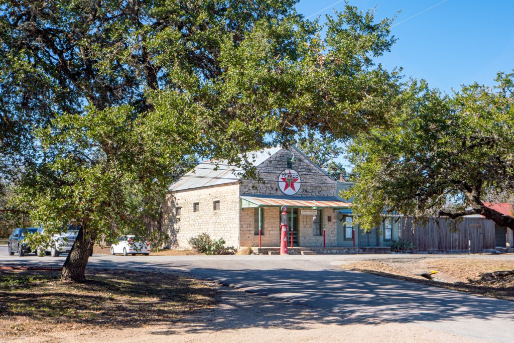 historic texaco station as seen from across the street with live oak trees in the foreground