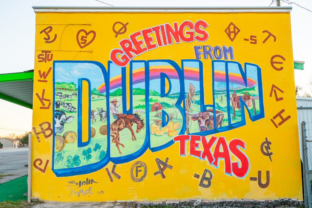 "bright yellow mural stating ""greetings from dublin texas"""
