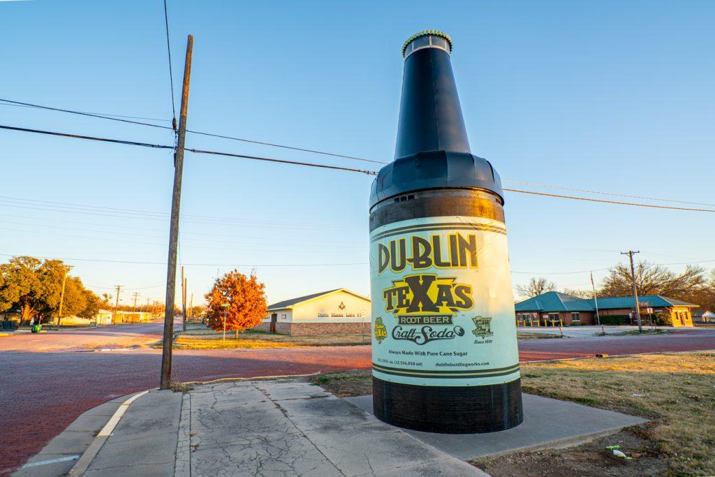 giant soda bottle on the corner of the road
