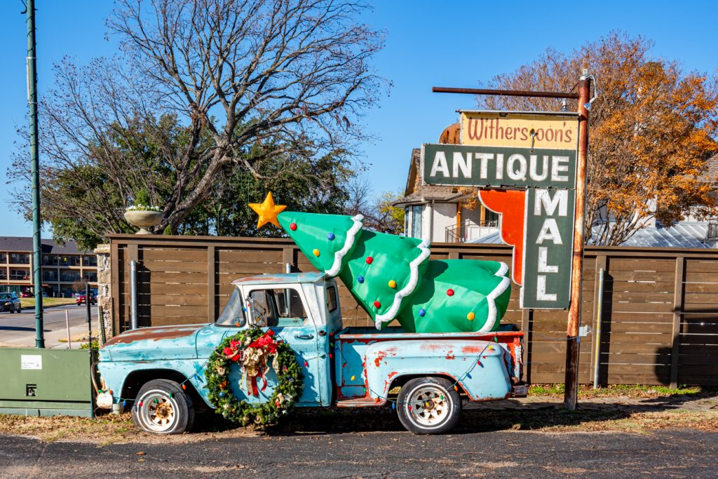 """historic truck in granbury with a plastic christmas tree in the back, sign says """"antique mall"""""""