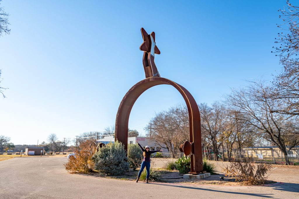 Kate Storm standing underneath the world's largest spur in lampasas tx, a texas roadside attraction