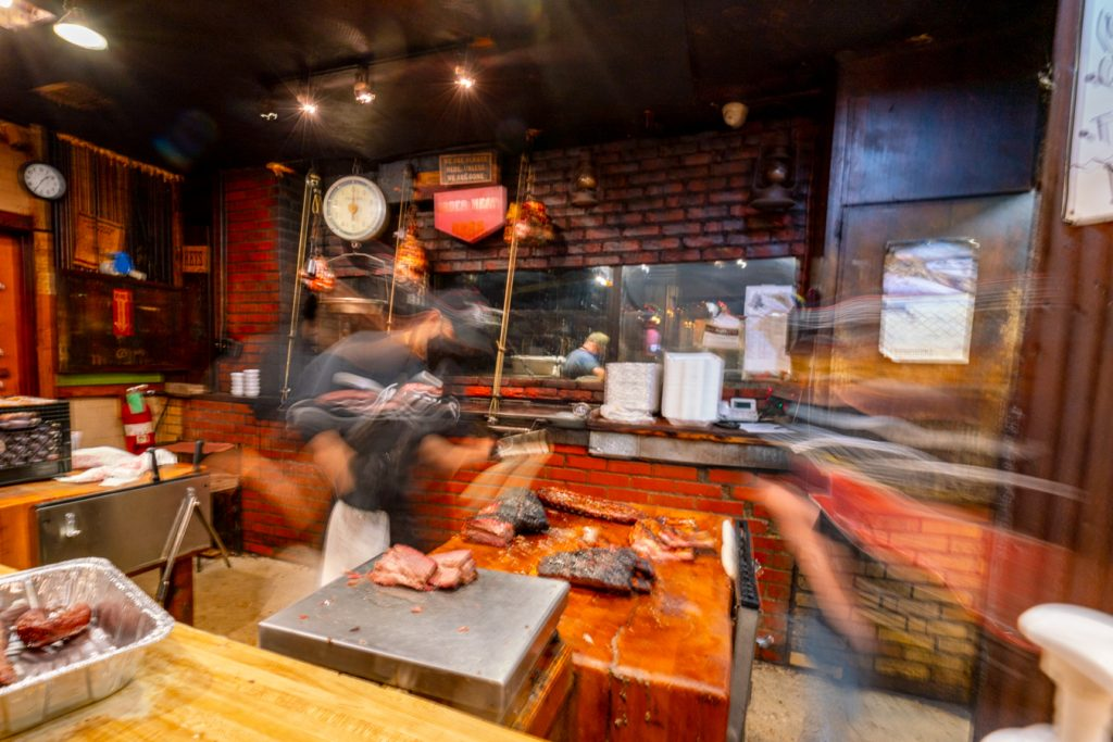 pitmaster rushing to serve brisket in a texas style bbq joint